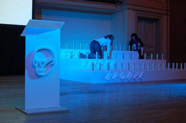 V popřadí scény pultík s reléfem loga pořádajícího Art Directors Clubu