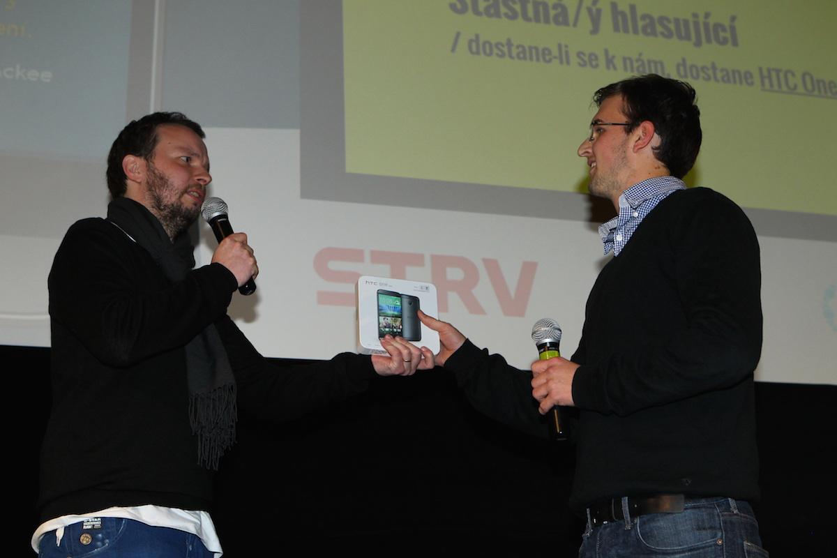 Hlasujícímu Petrovi náleží HTC One M8, předává Marek Prchal. Foto: Tomáš Pánek