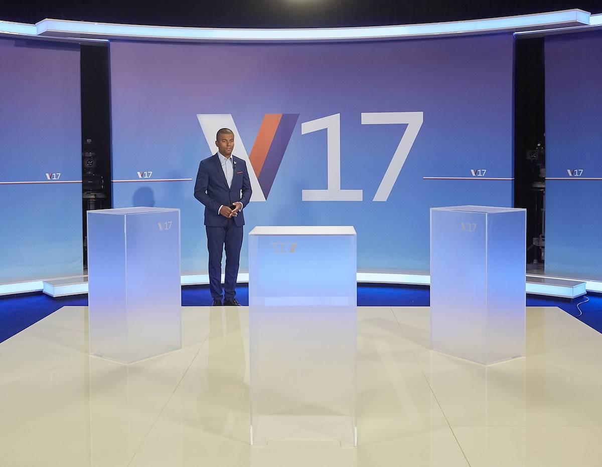 Rey Koranteng ve studiu pro volební Duel, jako moderátor bude stát u prostředního pultíku, zády ke kameře. Foto: TV Nova