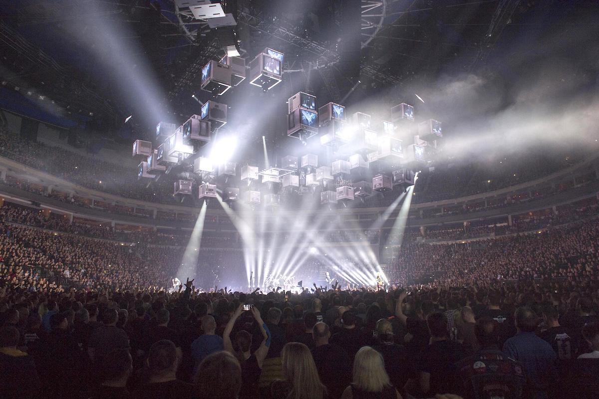 Metallica v O2 Areně. Nad pódiem uprostřed haly probíhala projekce na soustavu kostek zavěšených od stropu, postupně spouštěných a zase vytahovaných nahoru