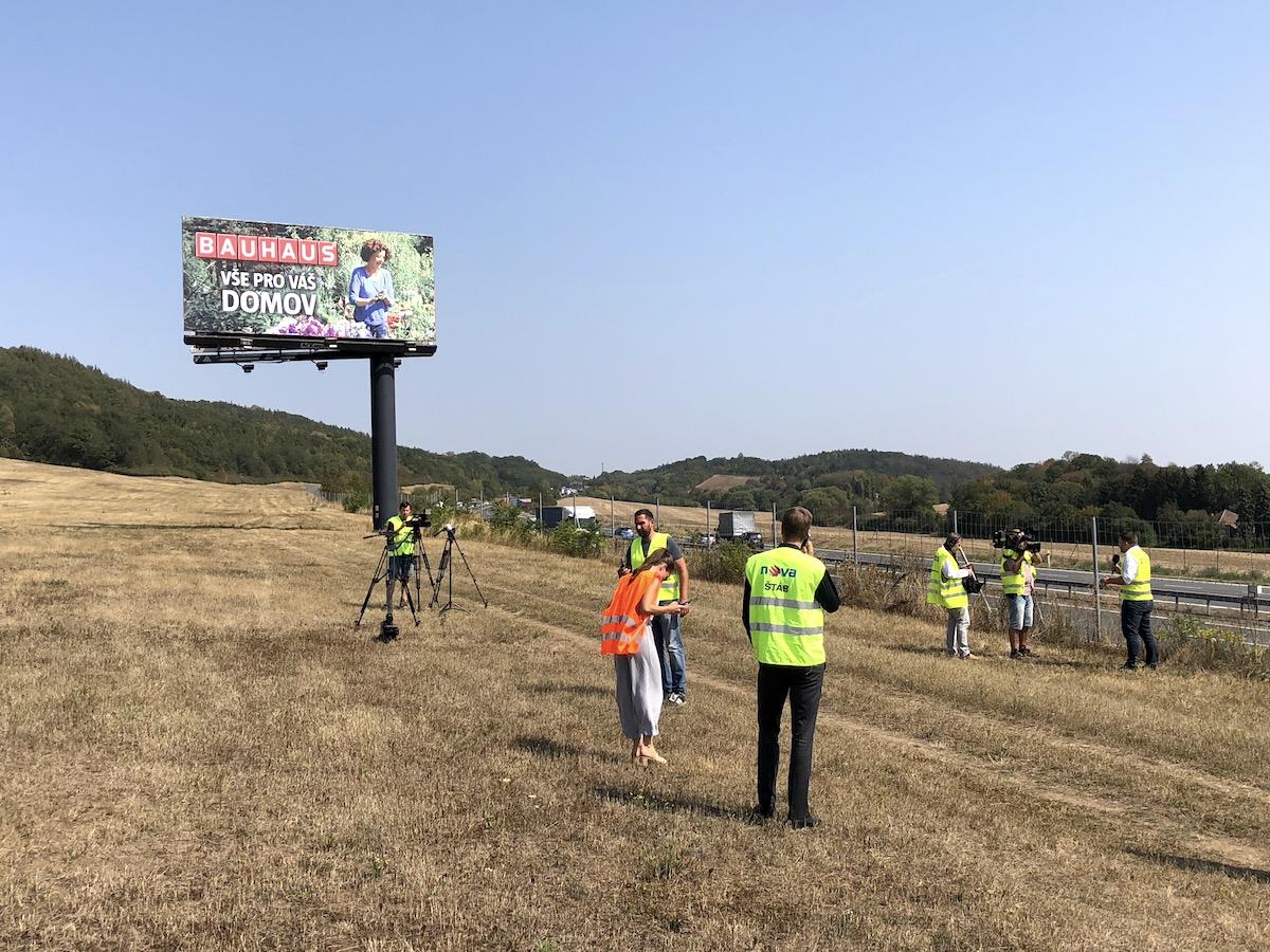 V pozadí stoji billboard společnost A.C.E. Media, která vede ohledně nosičů s Českem arbitráž