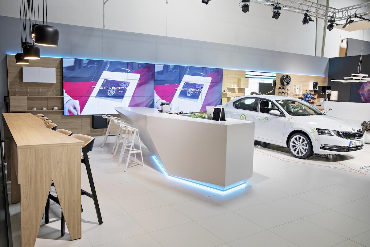 Digitální showroom Škody: co prodejce konfiguruje v tabletu, promítá se u bílého stolu s občerstvením zákazníkovi na stěnu s obrazovkami s rozlišením 4K