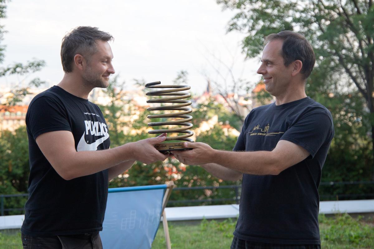 Zdeněk Buchtela (vpravo) přebírá putovní Zlaté pero od faráře Martina Hobzy